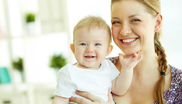 Frau hält ein fröhliches Baby in den Armen. © pressmaster, fotolia.com