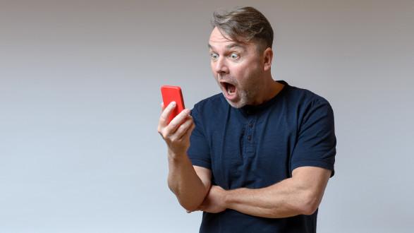 Mann blickt entsetzt auf sein Handy © Michael Heim, stock.adobe.com