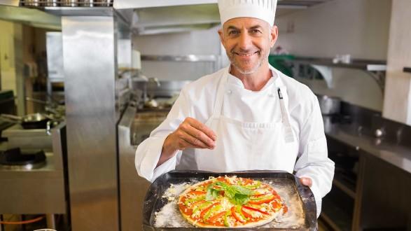 Koch in einer Küche mit Pizza am Blech © WavebreakMediaMicro, stock.adobe.com