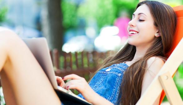 Junge Frau sitzt in einem Liegestuhl mit einem Laptop auf dem Schoß © pikselstock, stock.adobe.com