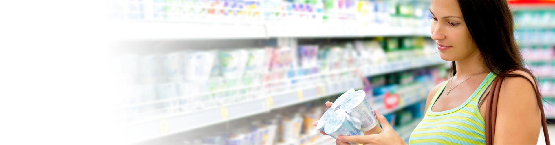 Frau steht im Supermarkt und prüft Joghurt © Korta, stock.adobe.com