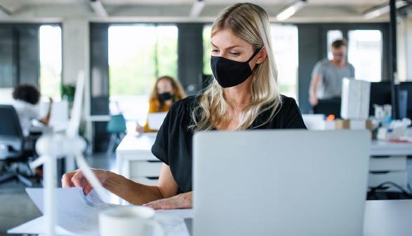 Frau mit Maske am Arbeitsplatz © Halfpoint, stock.adobe.com