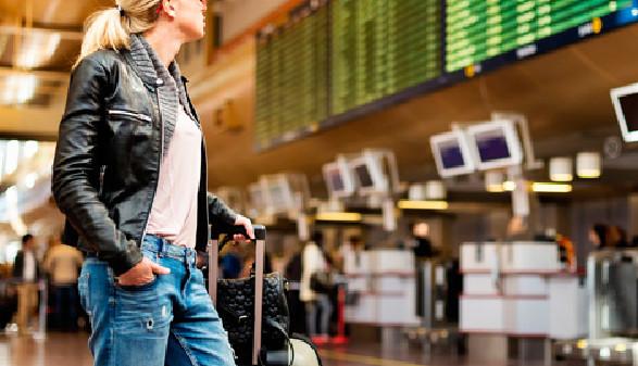 Frau mit Koffer schaut auf Monitor mit Abflugzeiten © -, panthermedia