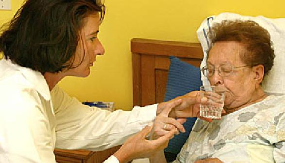 Pflegerin gibt der schwachen Pensionistin ein Glas Wasser. © Gina Sanders, Fotolia.com