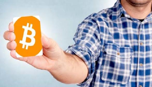 Mann mit Bitcoins-Card © badmanproduction, Fotolia.com