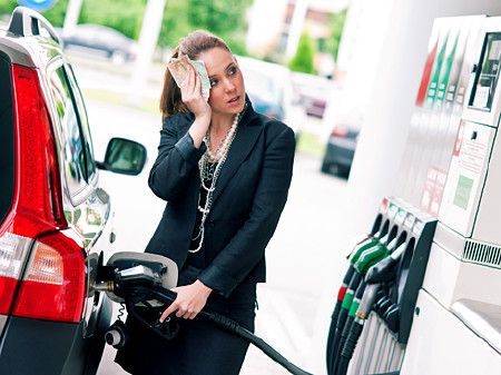 Frau steht neben der Zapfsäule und tankt ihr Auto voll. © bertys30, fotolia.com